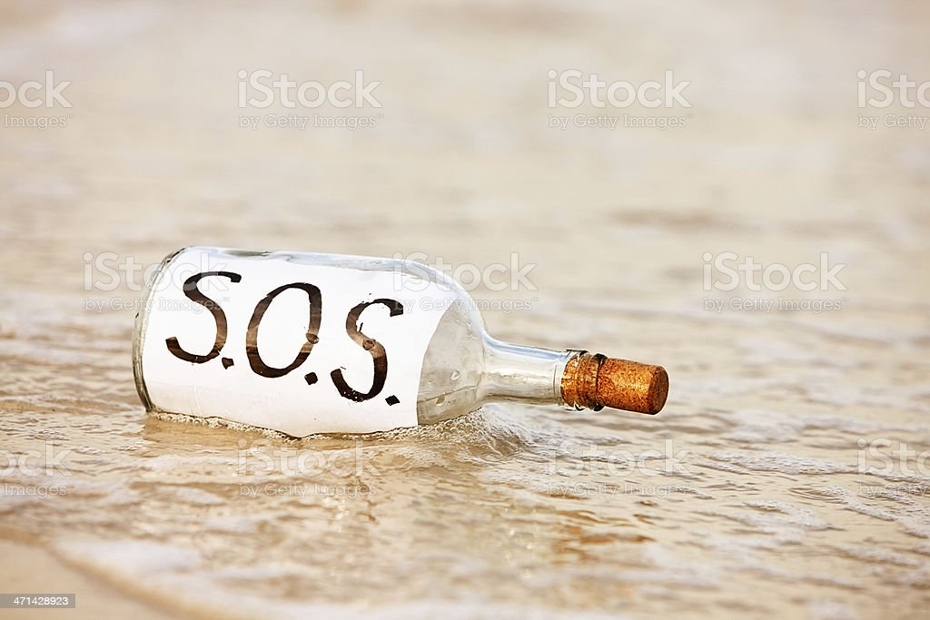 SOS message in bottle being washed away by tide royalty-free stock photo