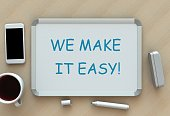 istock WE MAKE IT EASY!, message on whiteboard, smart phone and coffee on table 916788596
