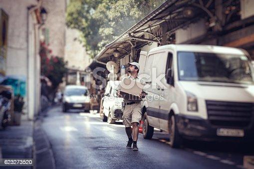 istock Messenger delivering parcel, walking in street next to his van 623273520
