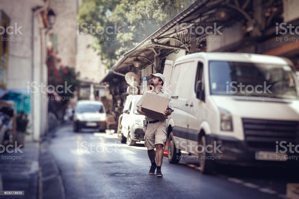 Messenger delivering parcel, walking in street next to his van stock photo