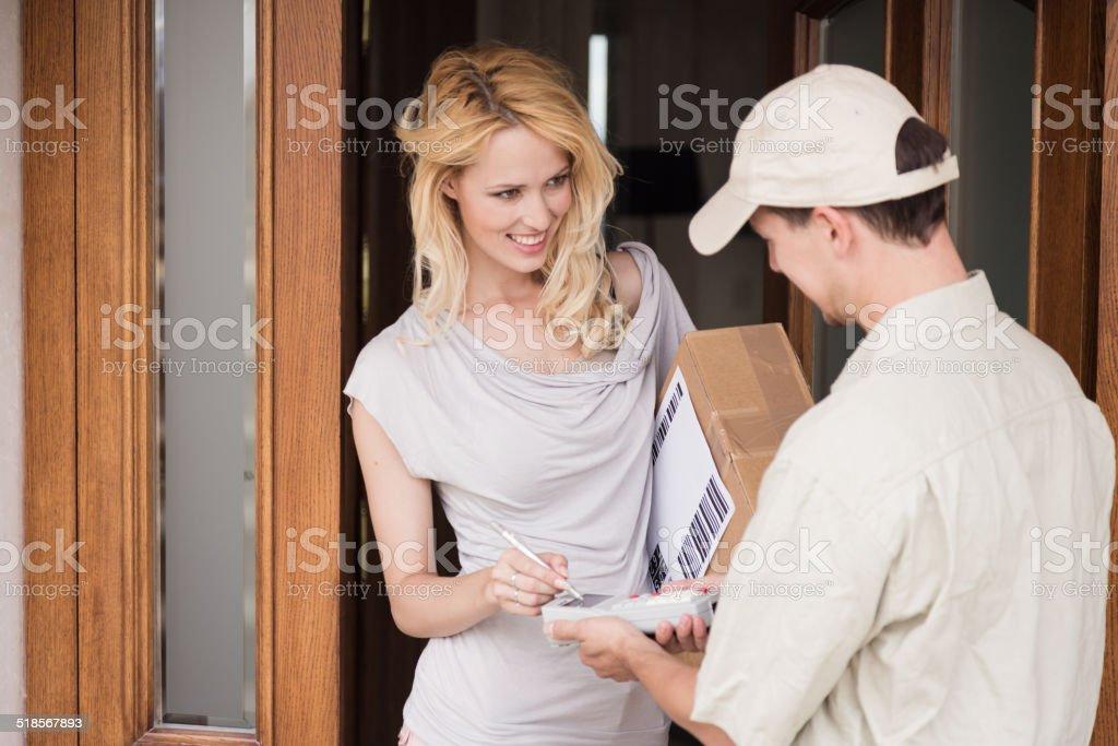 messenger handing parcel to customer stock photo