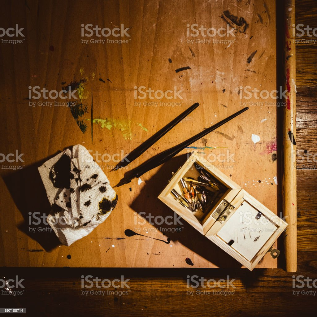 Messthetics: artist's workplace. Ink pens and the box with nibs on the easel covered by spots of paint and ink. stock photo