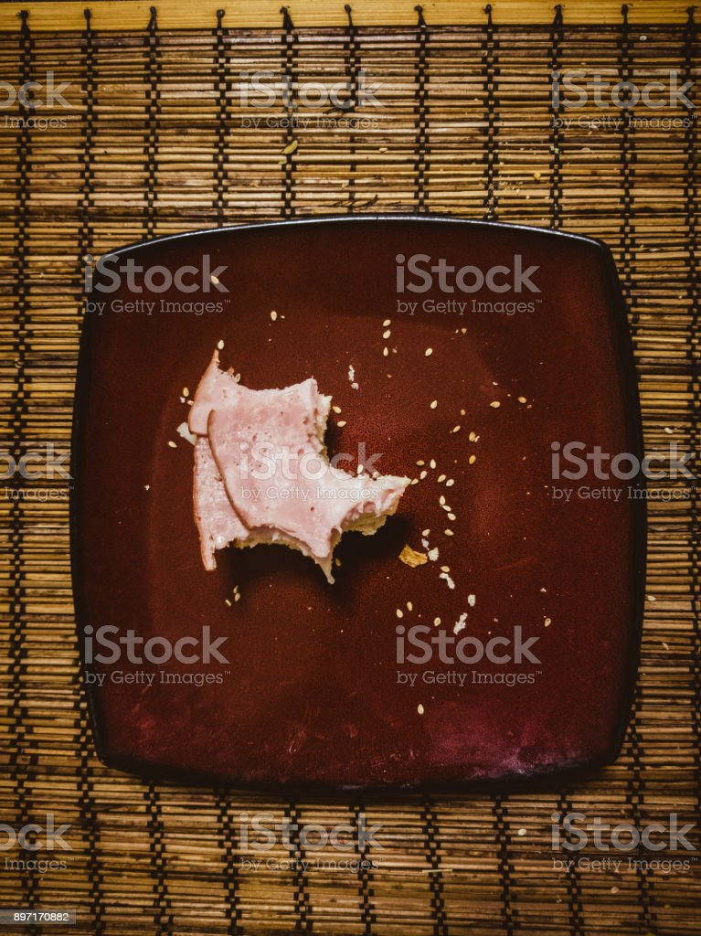 Messthetics food. Bitten unfinished sandwich with ham on the plate stock photo