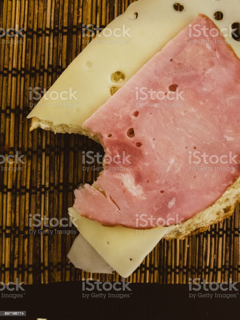 Messthetics food. The bitten sandwich with ham and cheese stock photo