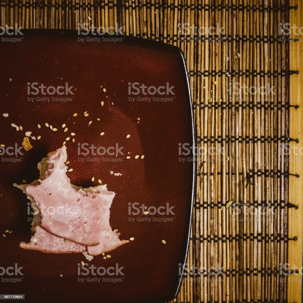 Messthetics food. Unfinished half-eaten sandwich with ham on the plate stock photo