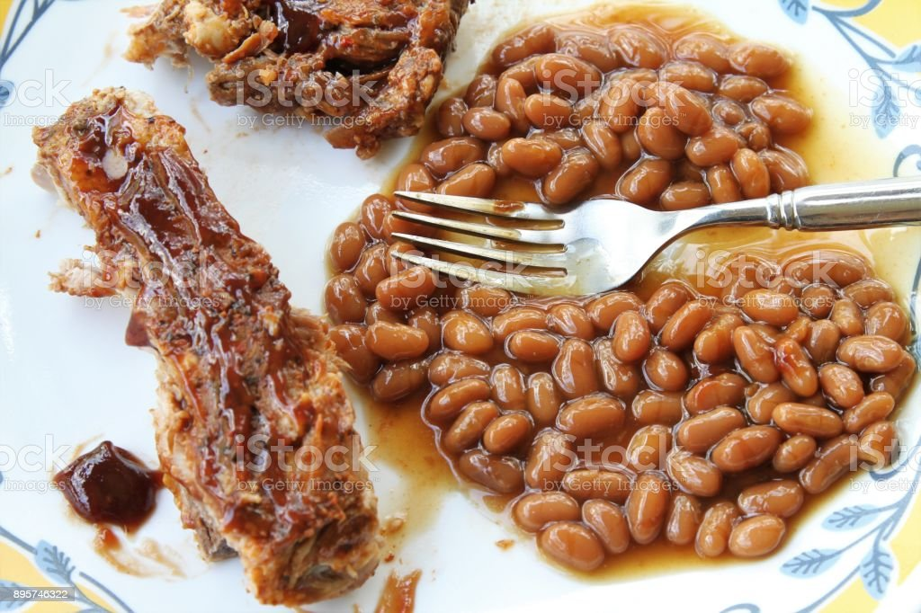 Messthetics - messy barbecue ribs and beans meal stock photo