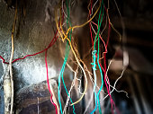 Close up color image depicting many colorful electrical wires dangling in a row in a chaotic mess. Room for copy space.