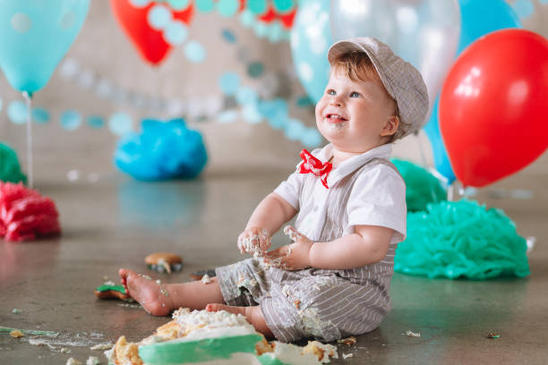 Messy baby boy eating cake on his 1st birthday looking up stock photo