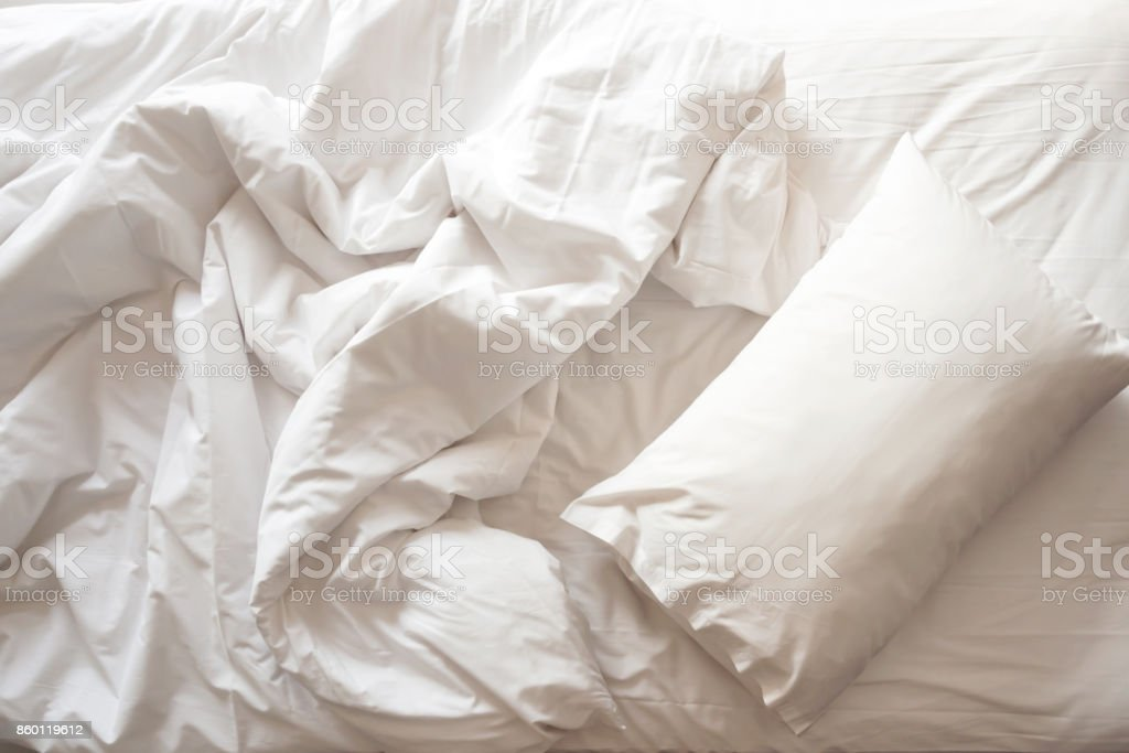Messy bed. White pillow with blanket on bed unmade. Top view. stock photo