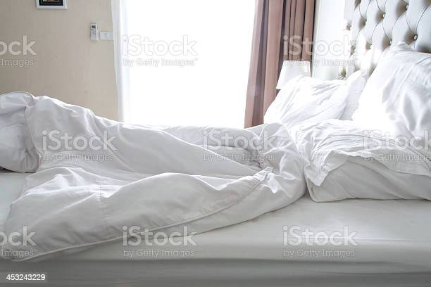 Messy Bedding Sheets And Pillow In Hotel Room Stock Photo - Download Image Now