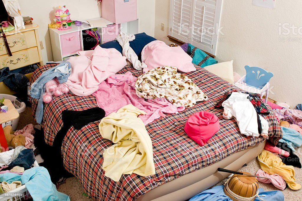 Messy bedroom with clothing thrown in disarray stock photo
