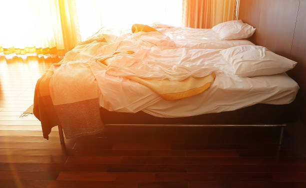 messy beds in a warm bedroom in the morning of sunshine day, sun light shining through big window, flare light added. - low lighting stock photos and pictures