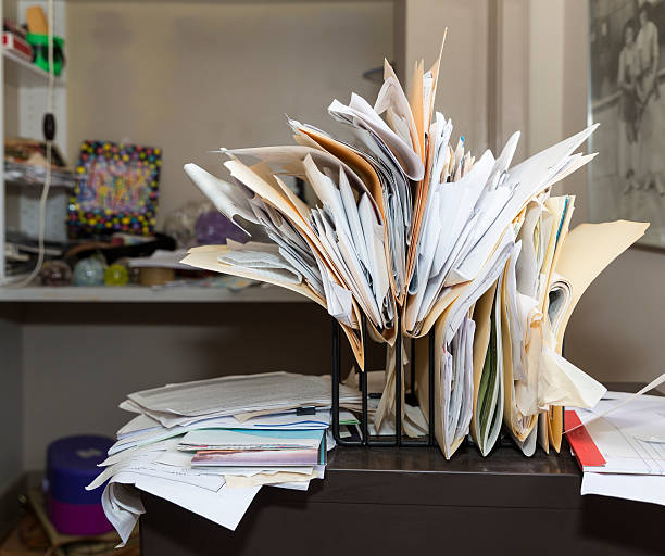 messy, chaotic, file rack on a desk in cluttered room - chaos stock pictures, royalty-free photos & images