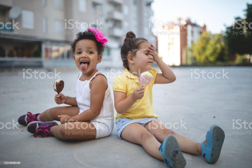 Messy children enjoying melting ice cream in summer stock photo