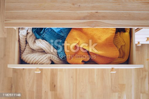 Open drawer with jeans and sweaters