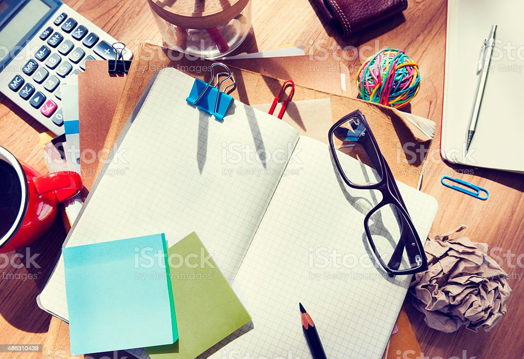 Messy Designer's Table with Blank Note and Tools stock photo