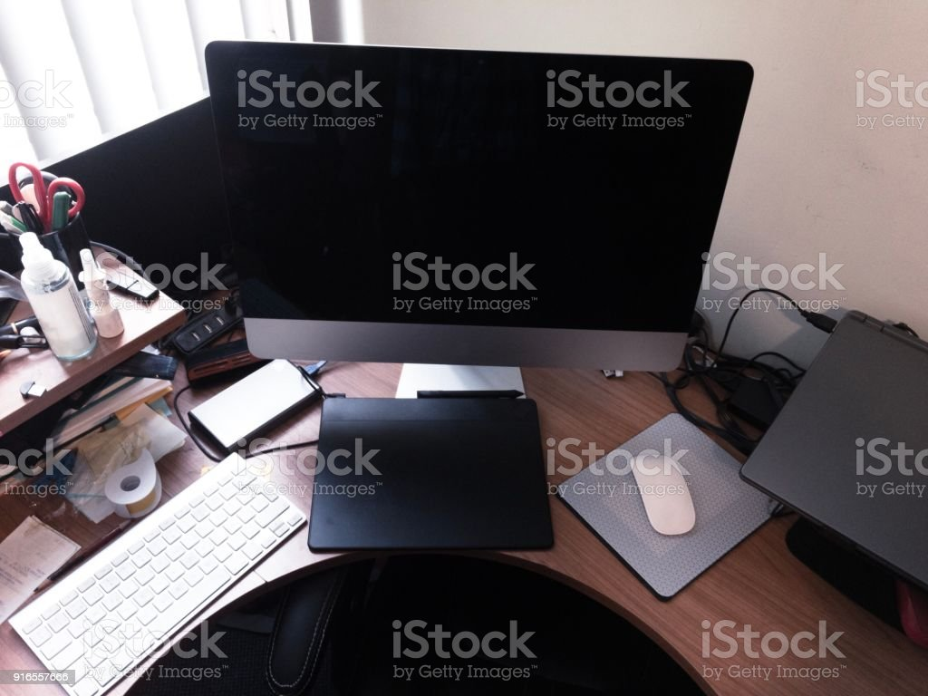 Messy desk of a creative artist two computers stock photo