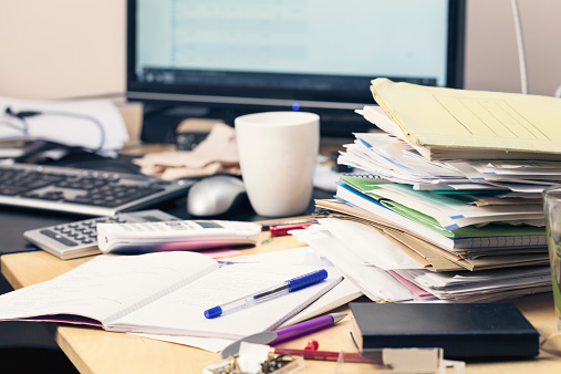 stack of brochures, files and documents, on mess desktop, monitor of pc in background