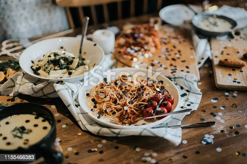 Messy dining table with leftover food covered with confetti after party celebration