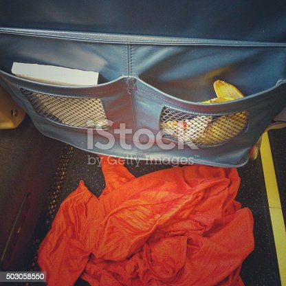 Messy passenger left dirty airplane passenger seat pocket behind with banana peel, trash, blanket on floor.