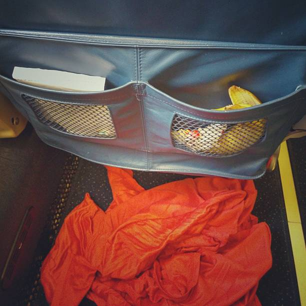 Messy Dirty Airplane Passenger Seat Pocket, Trash, Banana Peel, Blanket stock photo