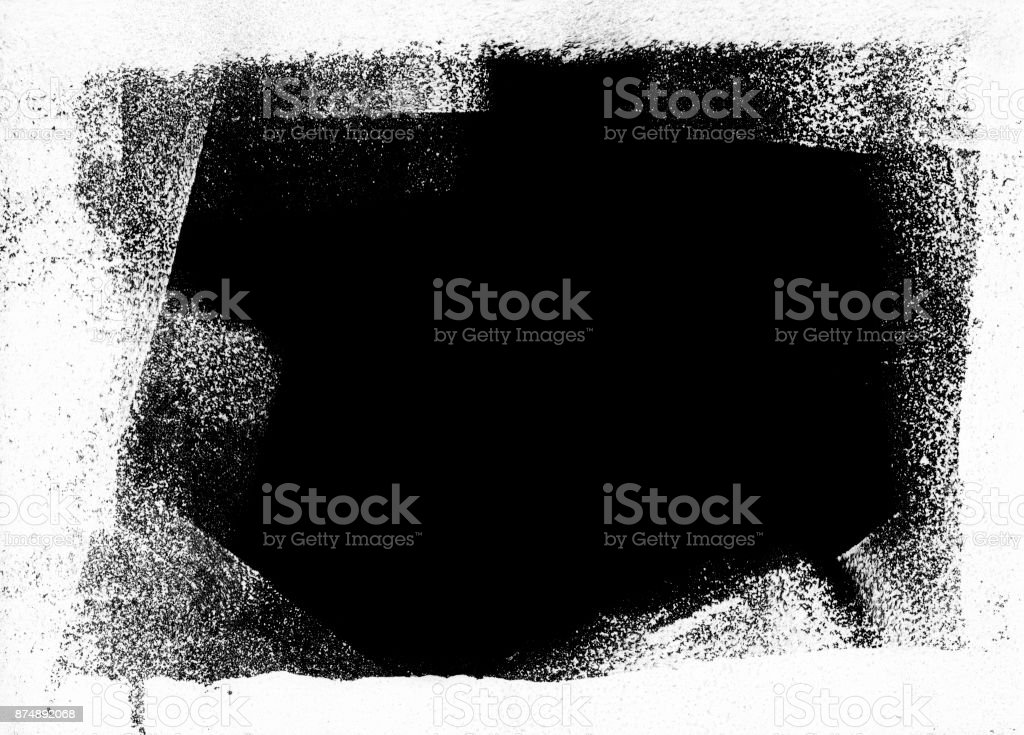 Messy dotted black painted stain on white paper background stock photo