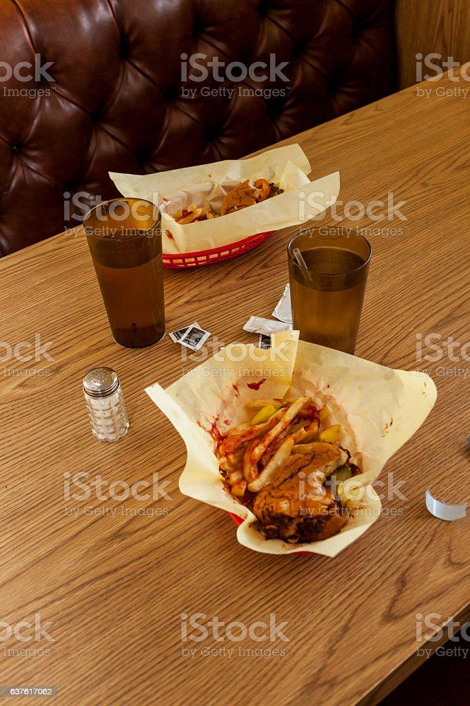 Messy fast food table restaurant hamburgers, drinks, fries stock photo