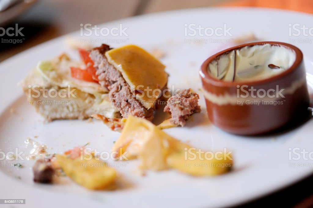 Messy food leftovers. Burger leftover on the plate after party stock photo