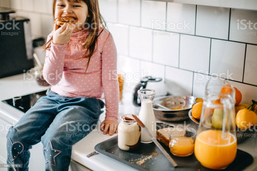 Girl having breakfast in kitchen