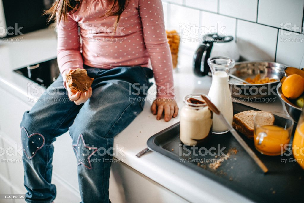 Girl having breakfast in kitchen