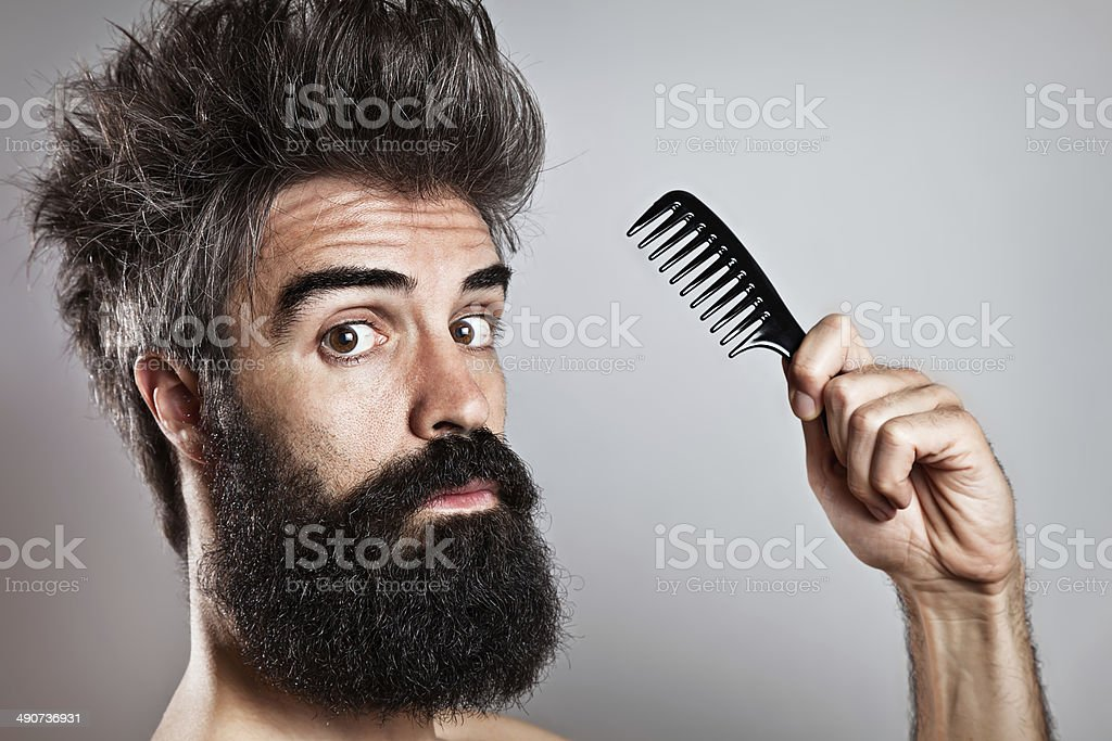 Messy haired bearded man holding a comb looking at came stock photo