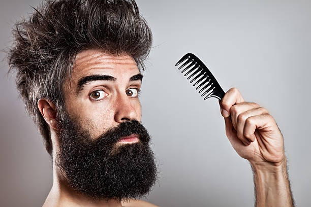 messy haired bearded man holding a comb looking at came - messy hair stock photos and pictures