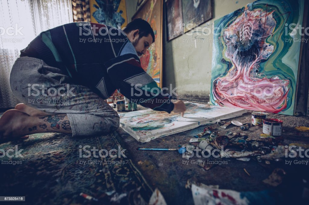 Young artist painting pictures in his room, living the life on an...