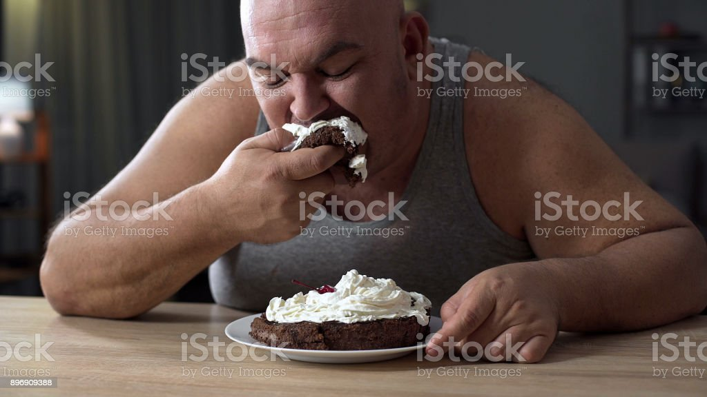 Messy obese man greedily eating cake with whipped cream, addiction to sweets stock photo