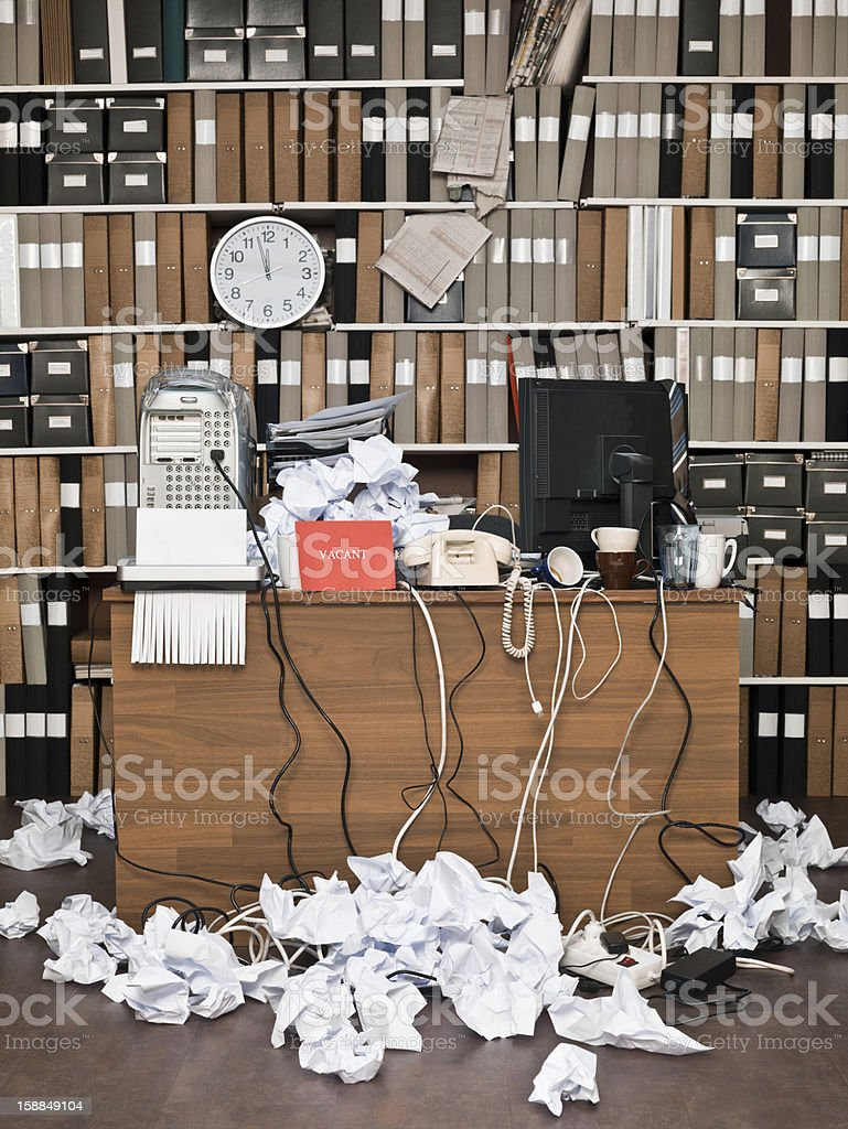 Messy office space with bookcase in the background stock photo