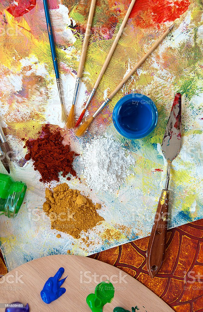 Messy paint palette with pigments and brushes royalty-free stock photo