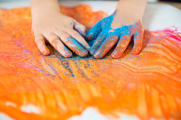 messy paint Child finger paints with glitter sand on his handshttp://2.bp.blogspot.com/-6uFsvUizzNg/T_85WkEZpeI/AAAAAAAABDs/ePjRC0VoP5M/s1600/kids.jpg sensory perception stock pictures, royalty-free photos & images