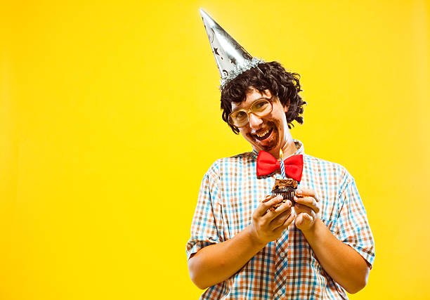messy party nerd teen boy holding cupcake frosting facial disaster - nerd boy eating stock photos and pictures