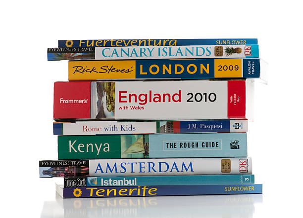 Messy pile of travel books on white background stock photo
