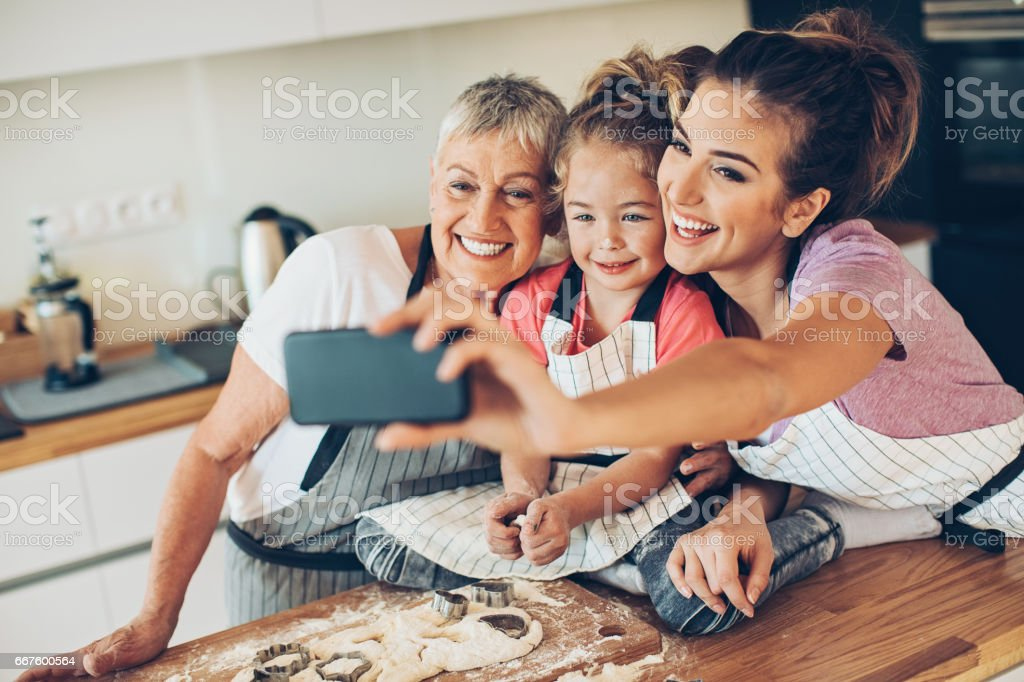 Grandmother, mother and a girl making selfie in a messy kitchen