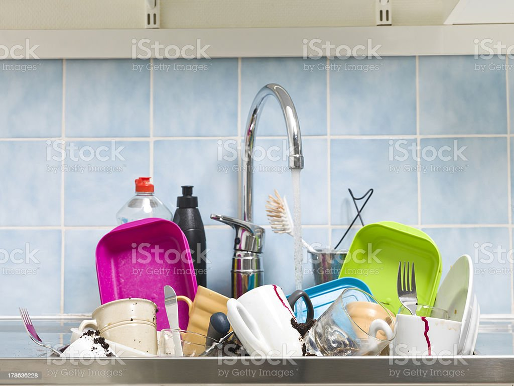 A messy sink full of dirty dishes with blue tile backsplash stock photo