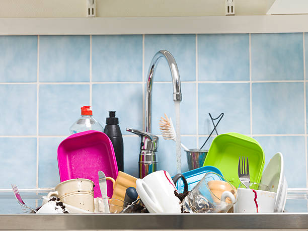 A messy sink full of dirty dishes with blue tile backsplash foto