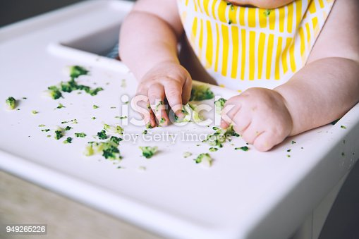 istock Messy smiling baby eats and tastes with fingers vegetables broccoli in high chair. 949265226