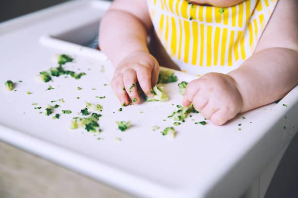 Bebé sonriente sucio come y sabe con brócoli verduras de dedos en la silla alta. - foto de stock