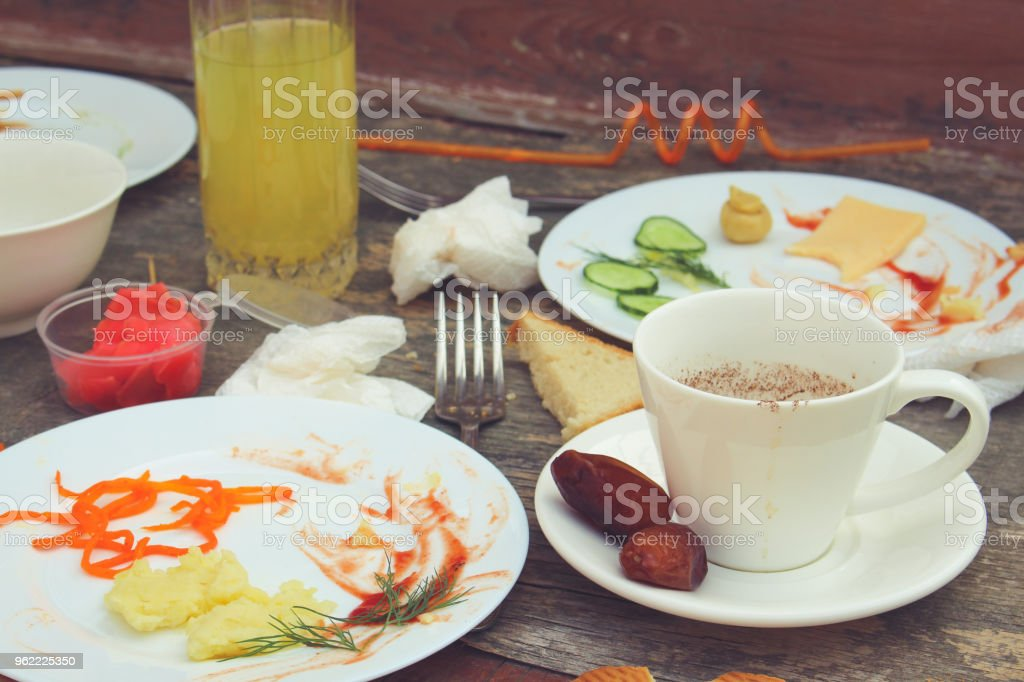 Messy table after party. Leftover food, spilled drinks, dirty dishes. stock photo