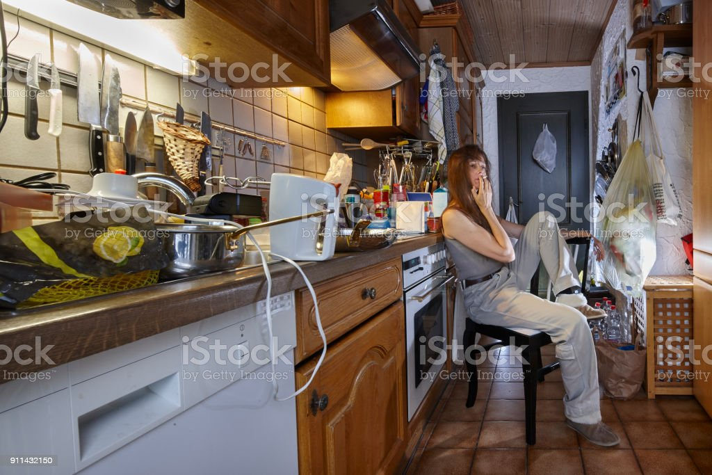 Smoking woman sitting in the kitchen on a chair.