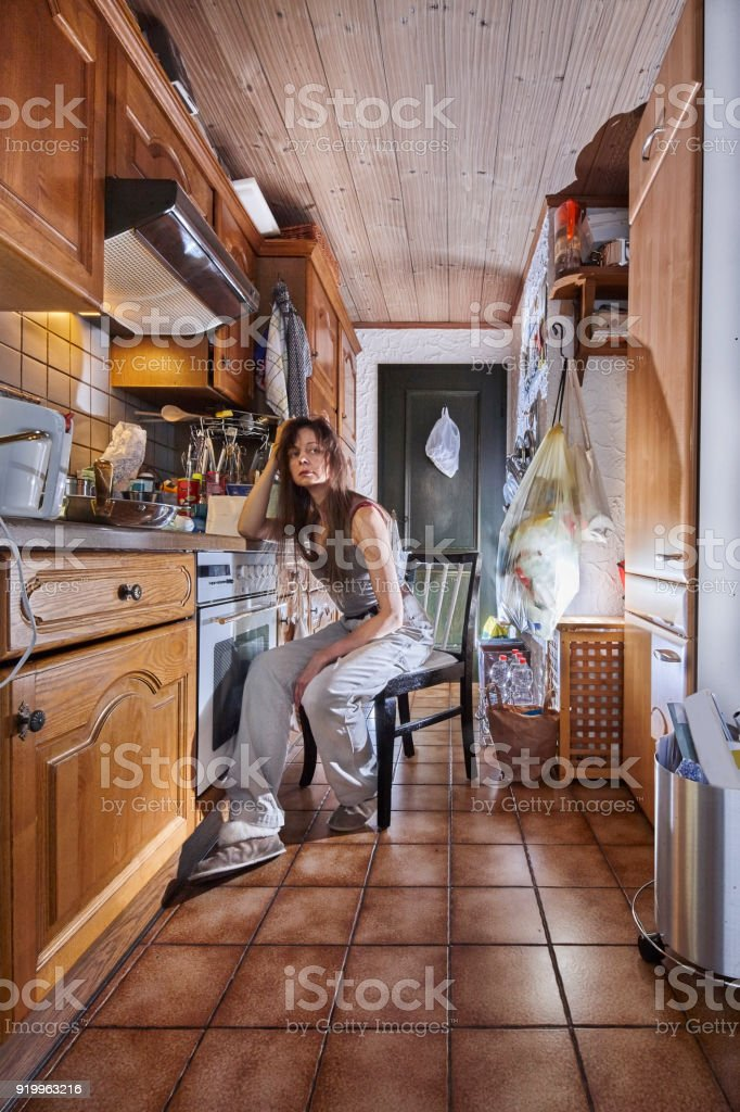 Woman sitting in the kitchen on a black white chair.