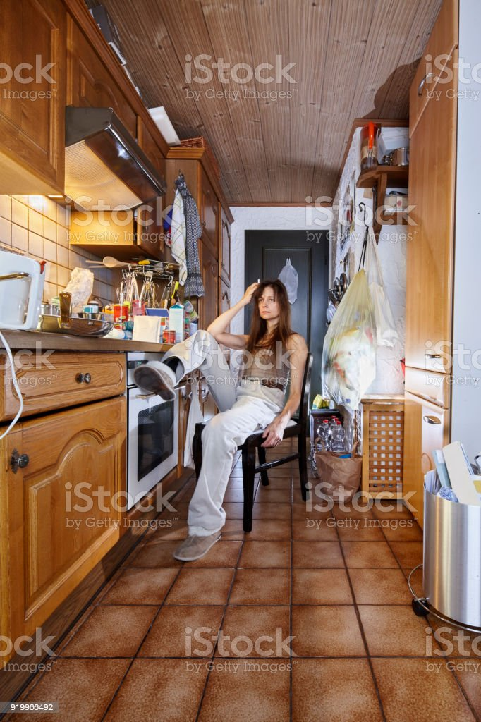 Woman smoking a cigarette and sitting in the kitchen on a black white...