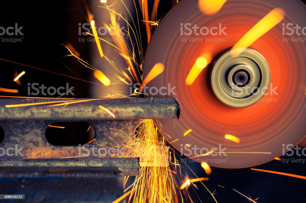 Metal bar being cut with electric grinder with sparks flying,...
