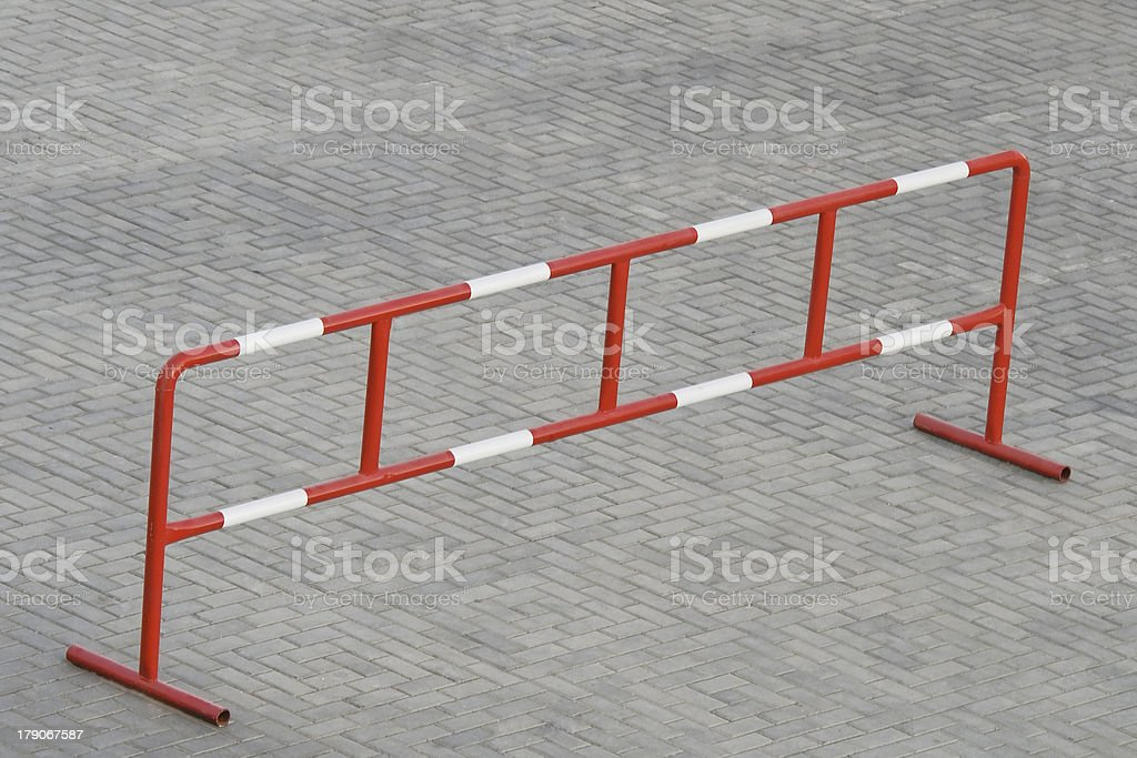 Metal barrier standing on the grey stone block paving royalty-free stock photo